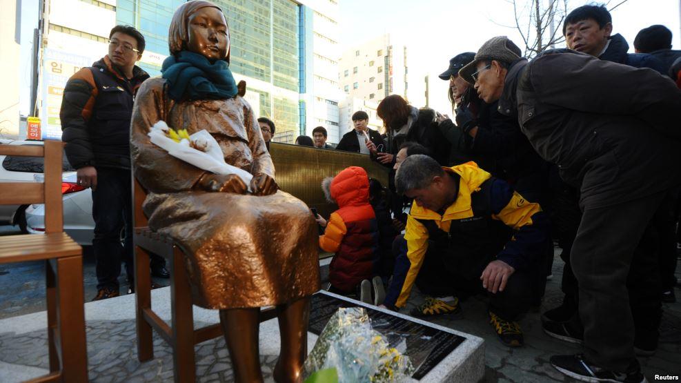 Foto: VOA Sebuah bunga diletakkan pada sebuah patung seorang gadis yang mewakili korban seksual oleh militer Jepang saat berlangsungnya unjuk rasa di depan Konsulat Jepang di Busan, Korea Selatan, 30 Desember 2016.