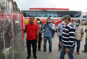 UJI COBA: Bupati Taput, Nikson Nababan menyaksikan para penumpang bus serta sopir yang akan disemprot di bilik dekontaminasi saat uji coba, Rabu (25/3).