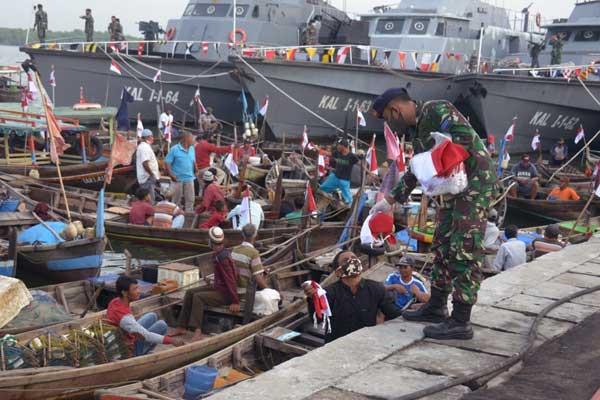 Bagikan Bendera: Komandan Lantamal I, Brigjen TNI (Mar), I Made Wahyu Santioso, membagikan bendera kepada para nelayan di Belawan.