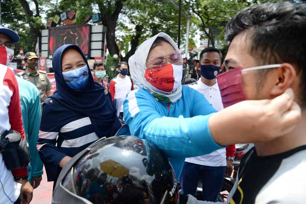 PAKAIKAN MASKER: Ketua TP PKK Sumut Nawal Edy Rahmayadi, memakaikan masker kepada salah seorang pengendara motor di acara Gerakan Bersama Pakai Masker atau Gebrak Masker serentak se-Indonesia, Senin (17/8).istimewa/sumu tpos.