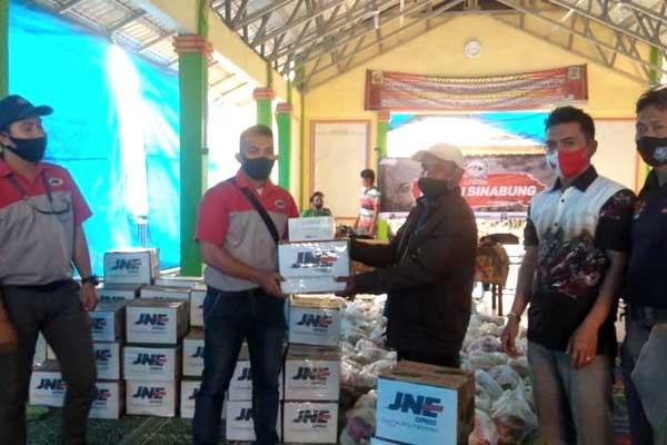 SERAHKAN: Pimpinan Cabang Utama JNE Medan, Fikri Al Haq Fachryana menyerahkan bantuan kepada perwakilan warga yang terdampak erupsi gunung Sinabung.