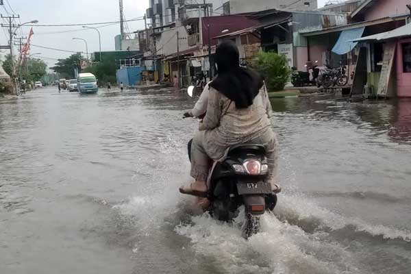 BANJIR ROB: Pengendara melintasi genangan air dari banjir Rob di kawasan Medan Utara, baru-baru ini.