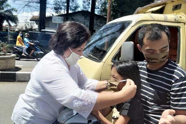 PAKAIKAN: Cory S Sebayang memakaikan masker pada seorang anak yang sedang melintas.
