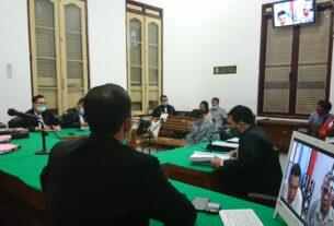 SIDANG: Oktavia Sihombing (tengah) dan dua terdakwa lainnya (layar monitor) menjalani sidang tuntutan, Jumat (25/9).