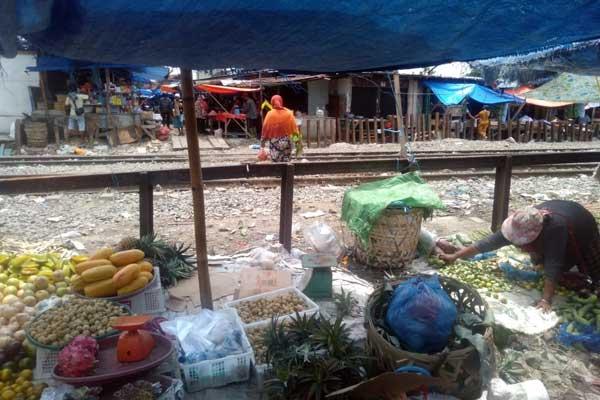 DITUTUP: Pedagang berjualan di depan jalan Riau Belawan yang ditutup plang besi oleh PT KAI.fachril/sumut pos.