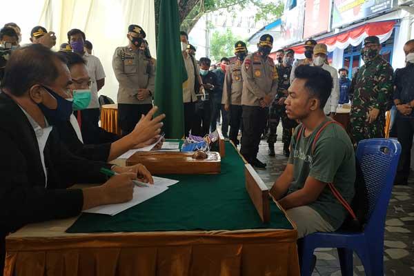 SIDANG: Seorang warga yang terjaring razia masker menjalani sidang lapangan oleh Hakim Pengadilan Negeri Medan di Lapangan Merdeka Medan, Selasa (16/9).