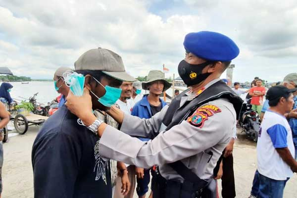 SOSIALISASI: Kasat Polairud Polres Langkat memakaikan masker kepada warga pesisir pantai pada kegiatan sosialisasi protokol kesehatan.