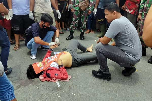 DIEVAKUASI: Jasad korban dikerumuni warga usai dievakuasi dari semak-semak usai dibunuh pelaku.