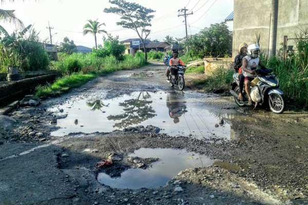 RUSAK PARAH: Pengendara sepeda motor melintasi Jalan Bakti ABRI di Kelurahan Besar, Kecamatan Medan Labuhan, yang rusak parah, Kamis (1/10). Hingga saat ini, Jalan Bakti ABRI tak kunjung diperbaiki.