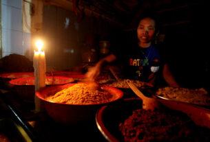 LISTRIK PADAM: Seorang pedagang bumbu merapikan barang dagangannya dengan penerangan sebatang lilin di Pasar Petisah Medan, belum lama ini.