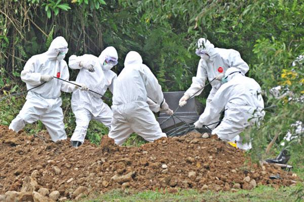 PEMAKAMAN: Petugas medis memakamkan jenazah pasien Covid-19 di lokasi pemakaman khusus di Simalingkar B, Medan Tuntungan.