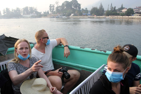 WISMAN: Sejumlah wisatawan mancanegara mengenakan masker saat menyeberang menuju pulau Samosir dari Pelabuhan Ajibata, Jumat (20/9).