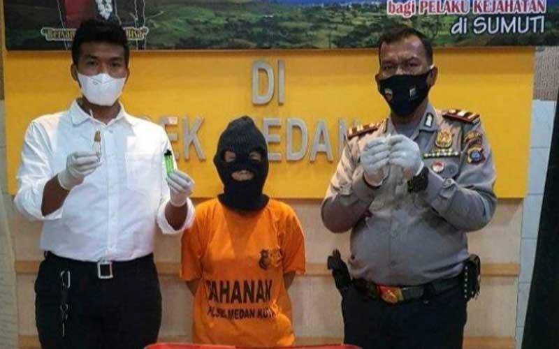 DIPAPARKAN: Tersangka E (tengah), tukang cuci pecandu sabu-sabu dipaparkan Polsek Medan Kota, Rabu (25/11).