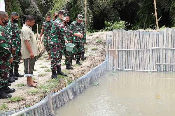 BERI MAKAN IKAN:  Dandim 0208/AS, Letkol Inf Sri Marantika Beruh memberi makan ikan lele yang ada di belakang Makodim, Minggu (15/11).