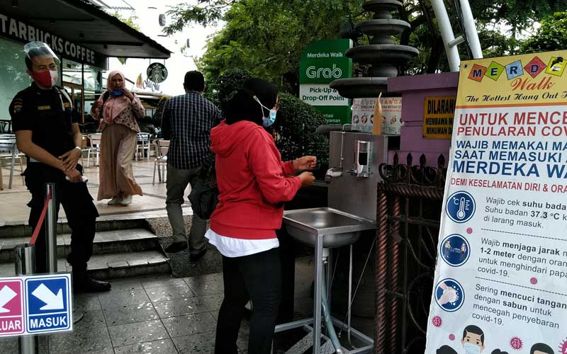 CUCI TANGAN: Pengunjung mencuci tangan di wastafel yang disediakan, sebelum memasuki kawasan Merdeka Walk, Jumat (27/11).