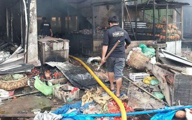 PERIKSA: Petugas Damkar memeriksa puing- puing sisa kebakaran Pasar Tingkat Berastagi. SOLIDEO/SUMUT POS.