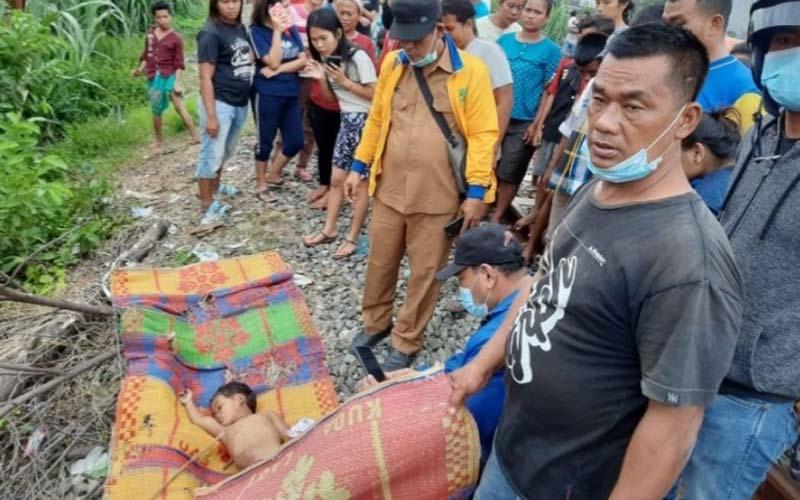 EVAKUASI: Petugas mengevakuasi jasad Athan yang tewas digilas kereta api di Jalan Elang Ujung, Medan Jumat (13/12).