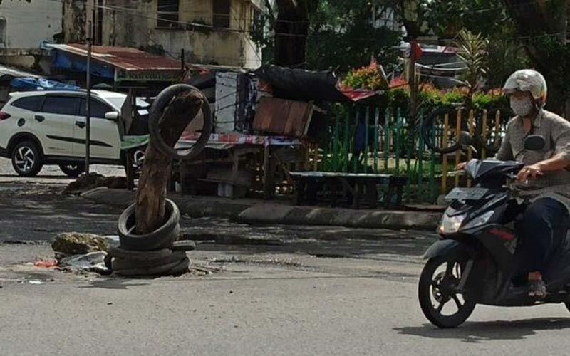 BATANG POHON: Jalan berlubang di Jalan Sutomo,  Pusat Pasar, Medan Kota ditimbun batang pohon oleh warga.istimewa/sumut pos.