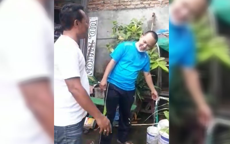 MENGALIR DERAS: Muhammad Rifai, pelanggan PDAM Tirtanadi  menunjukkan air yang mengalir deras dari kerannya.  teras rumahnya, Sabtu (2/1).ISTIMEWA/sumu tpos.