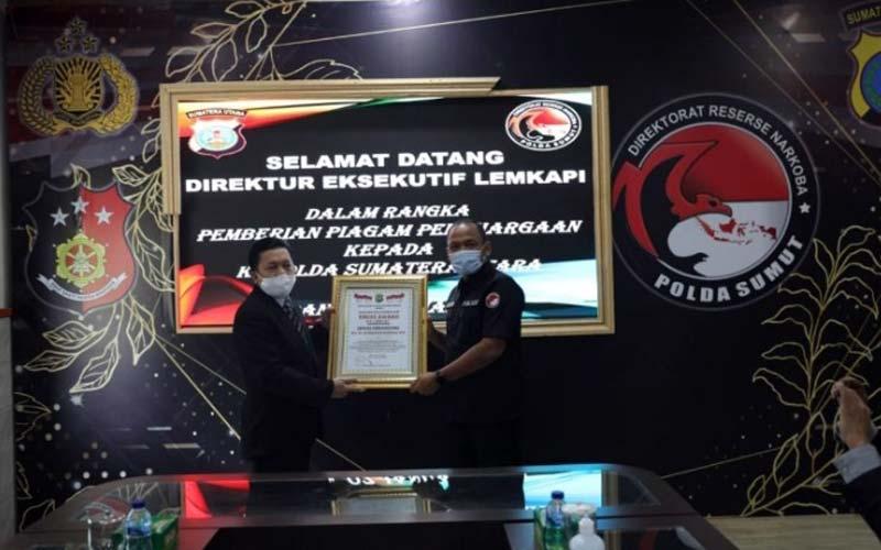 PIAGAM: Mewakli Kapoldasu, Dir Resnarkoba Poldasu,  Kombes Pol C Wisnu Adji P menerima  piagam penghargaan Trust Award.dewi/sumut pos.