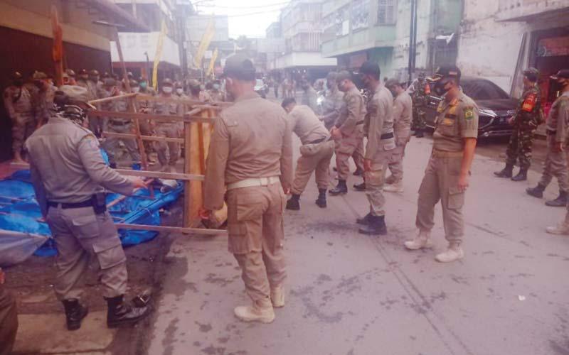 PENERTIBAN: Satpol PP saat menertibkan pedagang kaki lima di Pasar Petisah. Penertiban tersebut berlangsung damai tanpa penolakan pedagang.