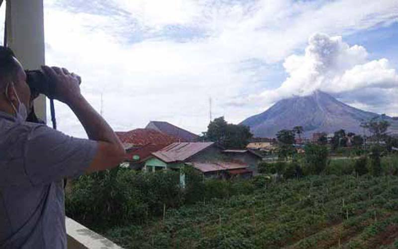 PANTAU: Petugas memantau aktivitas erupsi Gunung Sinabung dari Pos Pemantau, Senin (4/1). Kemarin, Gunung Sinabung kembali erupsi dengan ketinggian kolom abu mencapai 800 meter.